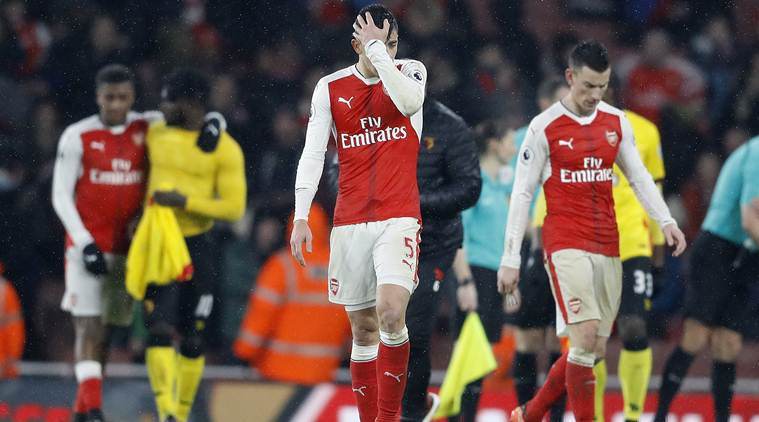 Dejected Arsenal players walk off the field after a defeat at the Emirates Stadium
