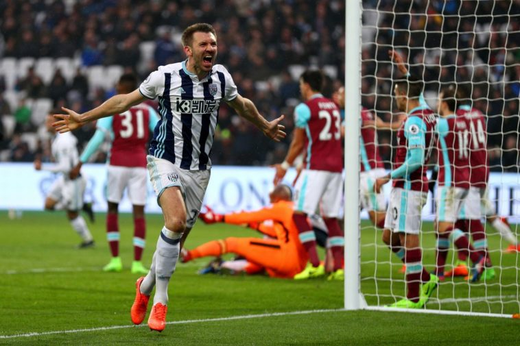 Gareth McAuley celebrates a late equaliser for WBA against West Ham at the London Stadium in the Premier League